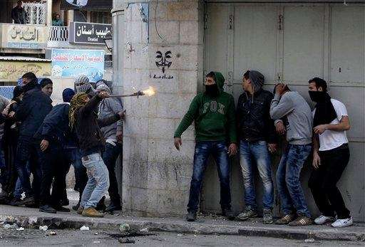 Palestinians take cover during clashes with Israeli troops