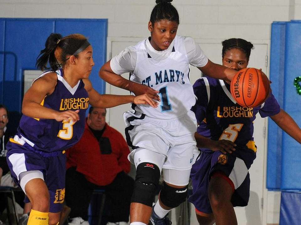 St. Mary's Jordan Agustus, center, looks to dribble