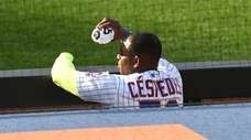 Mets' Yoenis Cespedes watches from the dugout against