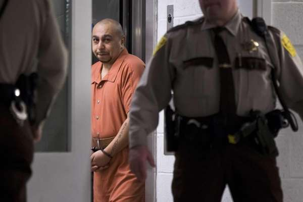 Julio Acevedo is escorted from a hearing at