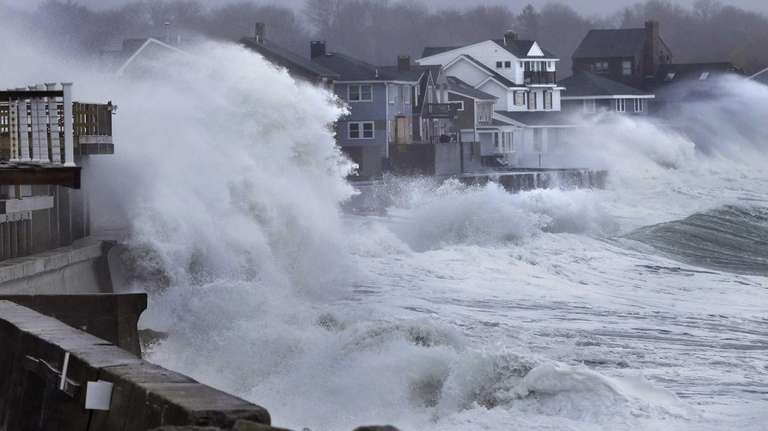 Ocean waves crash over a seawall and into