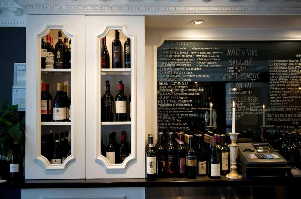 White cabinets house the many wines Molto Vino