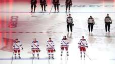 Members of the Rangers and the Hurricanes stand