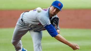 Mets starting pitcher Jacob deGrom works during the