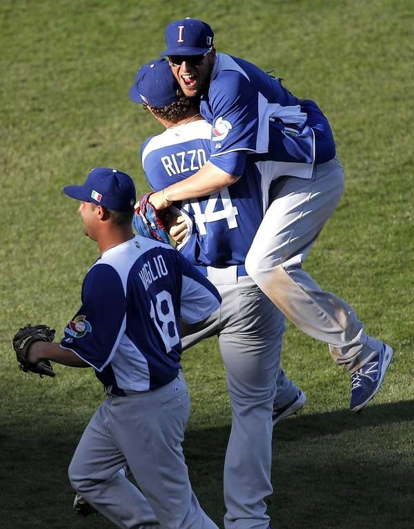 Italy's Alex Liddi jumps onto teammate Anthony Rizzo