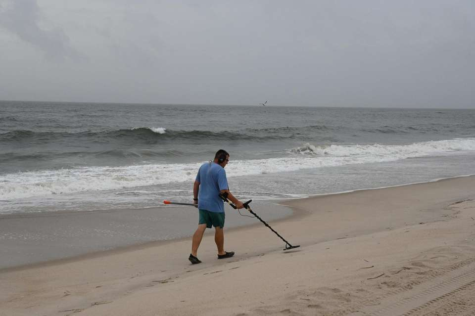A man uses a metal detector on field