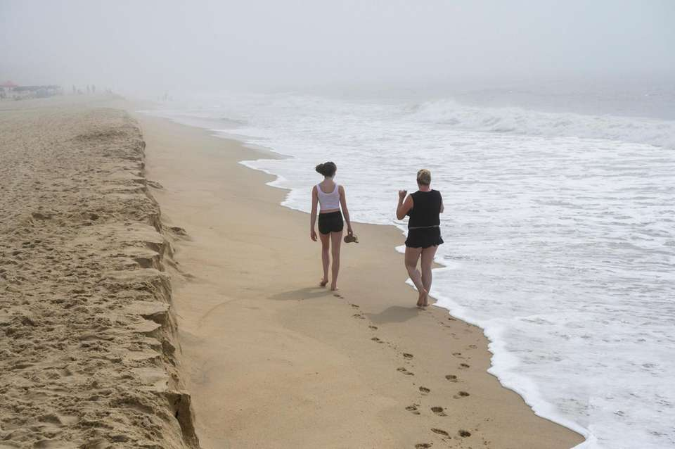 Two women walk along the beach at Nick's