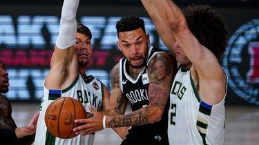 Nets guard Chris Chiozza cuts between Bucks guard