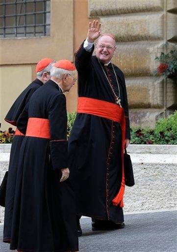 Cardinal Timothy Dolan waves to reporters as he