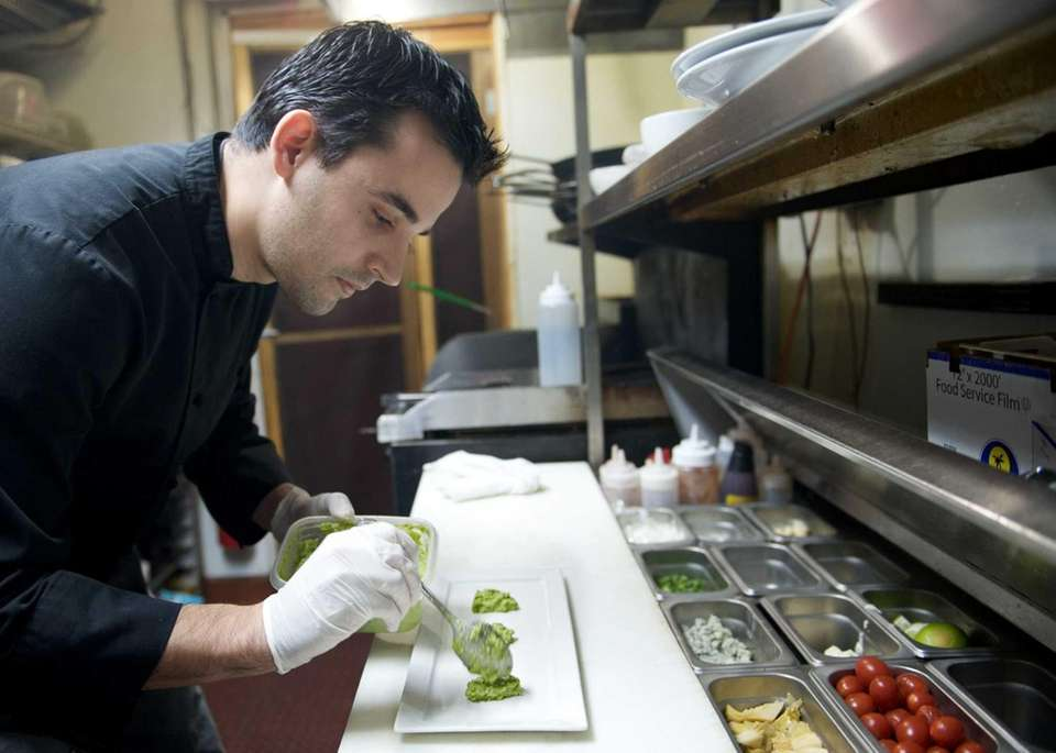 Chef Bruno Oliveira plates an order in the