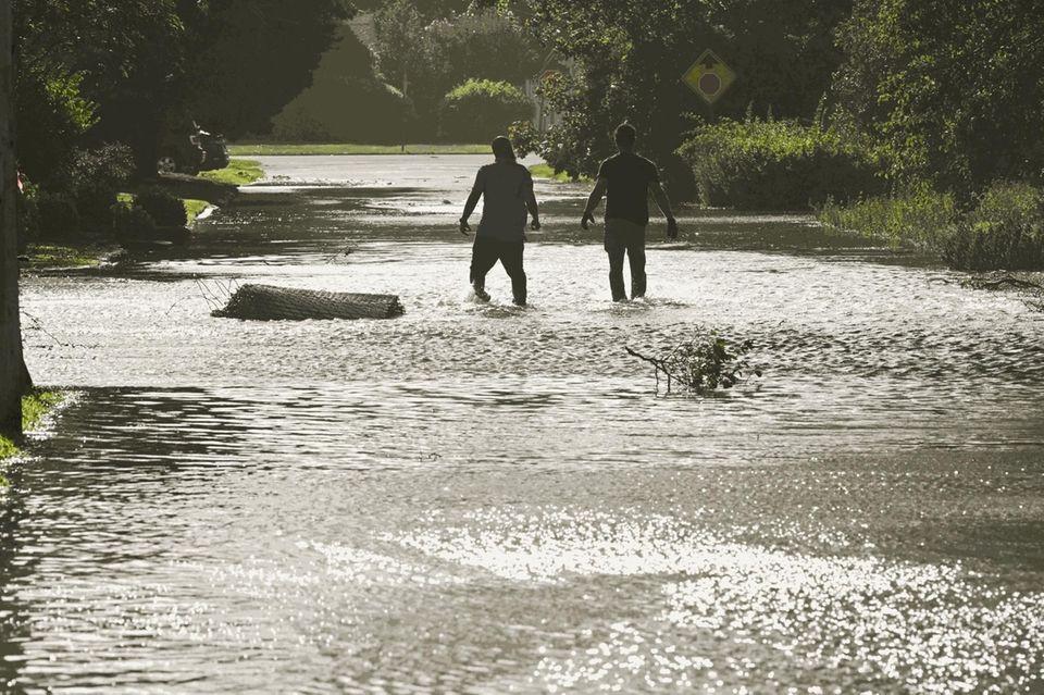 Two men wade through water on Harriet Rd.