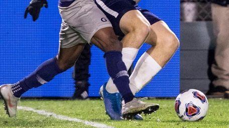 Georgetown's Achara  chases down Virginia's Axel Gunnarsson,