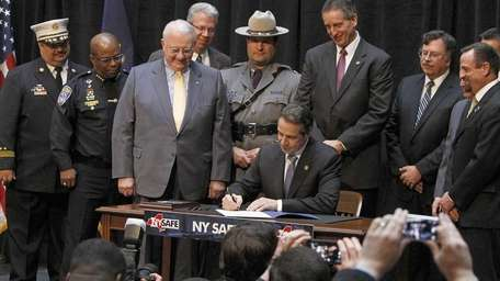 Gov. Andrew M. Cuomo, seated at center, signs