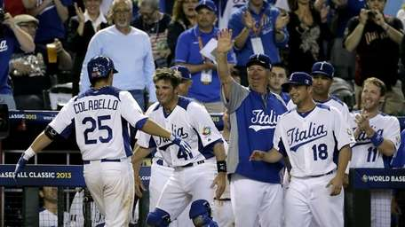 Italy's Chris Colabello celebrates with teammates after hitting