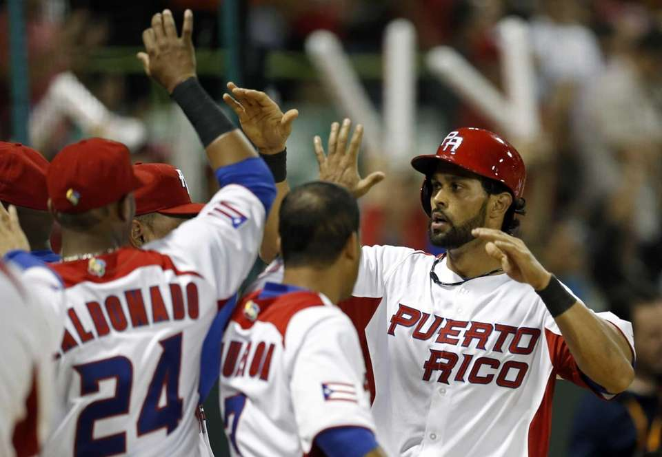 Puerto Rico's Angel Pagan, right, highs five with