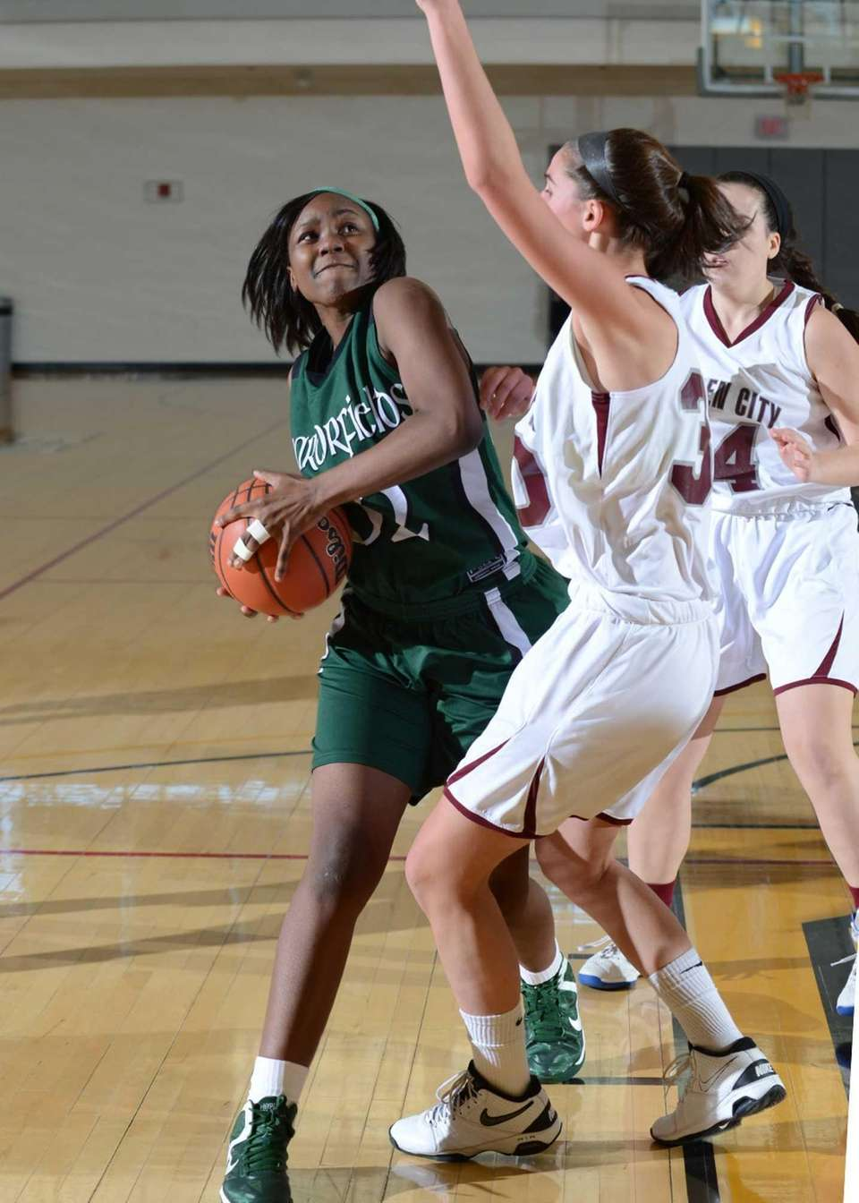 Harborfield's Donasja Scott (left) under pressure goes up
