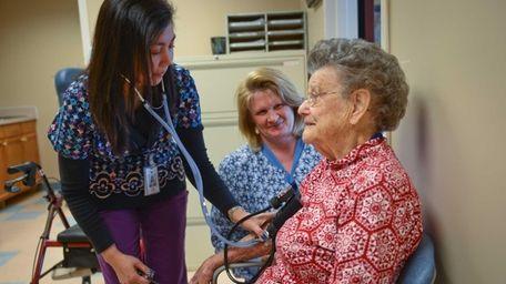 Emergency Nurse, LPN, Luz Pingco, left, takes a