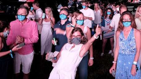 Some concertgoers stand at a VIP area during