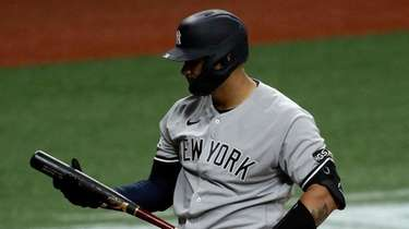 The Yankees' Gary Sanchez, right, reacts after striking