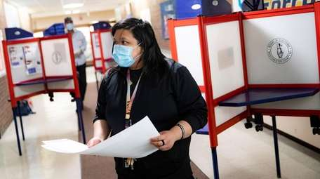 A voter wears a protective mask while casting
