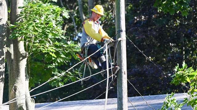 A PSEG worker works on restoring power in