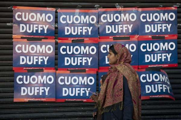 A woman walks past the campaign signs of