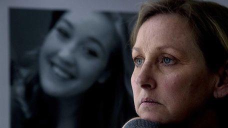 Susan Roethel sits alongside a photo of her