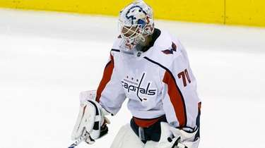 Capitals goaltender Braden Holtby takes a helmet off
