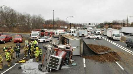 A dump truck overturned Monday, spilling dirt and