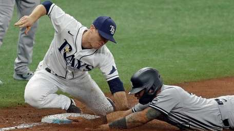 Rays third baseman Joey Wendle, left, tags out