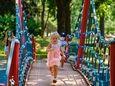 Lilly Wylaz, 3, runs across a suspension bridge