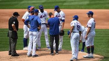 A New York Mets trainer checks on starting