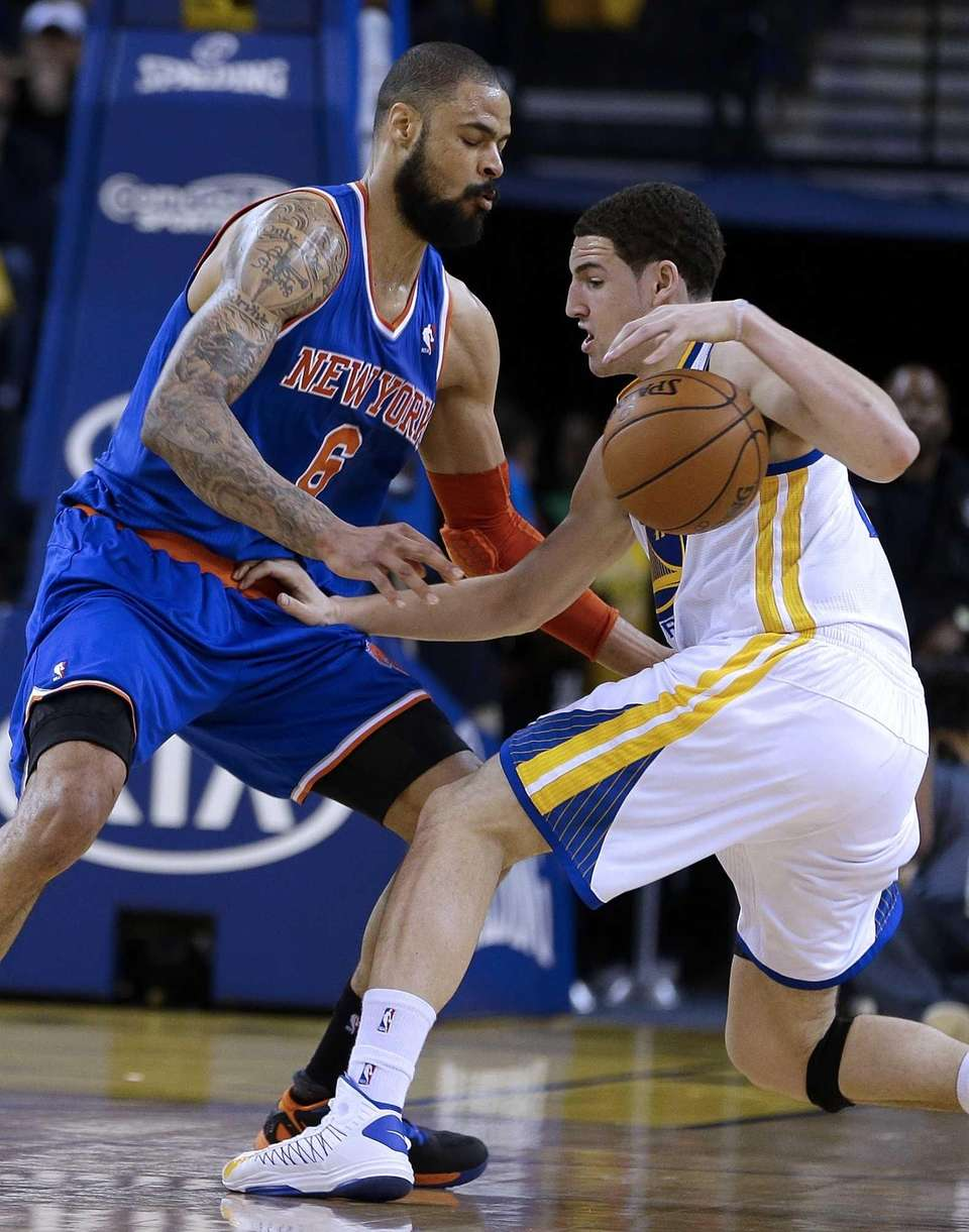 The Golden State Warriors' Klay Thompson, right, drives