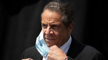 New York Gov. Andrew Cuomo removes a mask