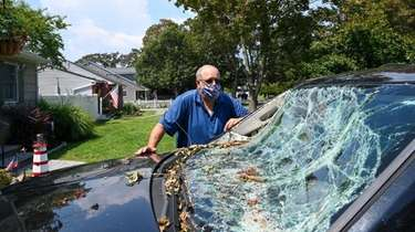 Joe Innace, next to his damaged vehicle outside