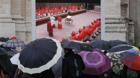 People watch cardinals assembled in the Sistine Chapel