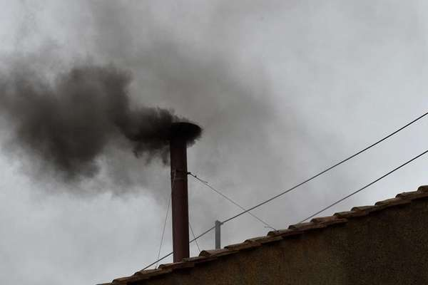 Black smoke rises from the chimney of the