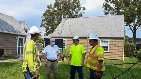 Homeowner Alex Chisholm talks to ulility electrical workers