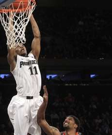 Providence's Bryce Cotton (11) dunks as Cincinnati's JaQuon