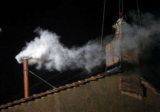 White smoke emerges from the chimney on the