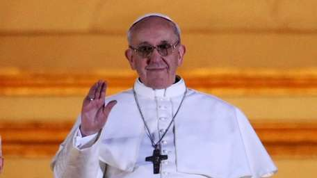 Newly elected Pope Francis appears on the central