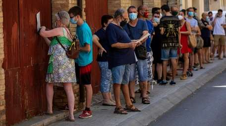 People wearing face masks queued up Monday to