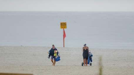 Beachgoers in Long Beach Thursday leave just before