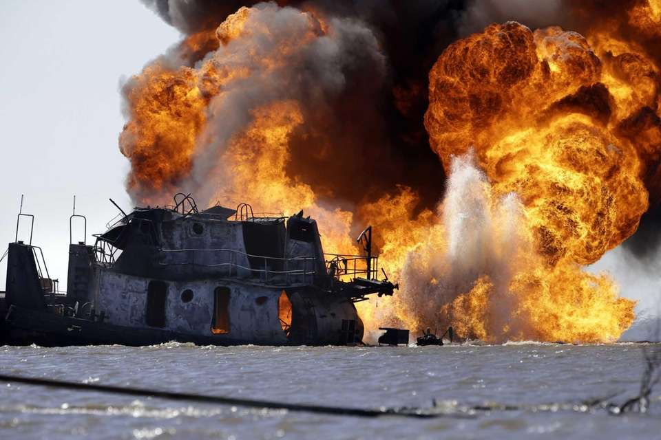 A fire burns Wednesday after a tugboat and