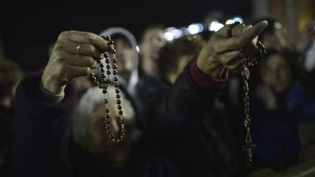 Women hold rosaries at St Peter basilica during