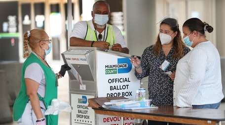 Poll workers at a Miami-Dade County ballot drop
