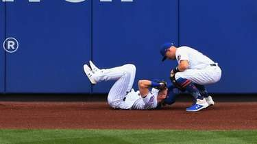 Mets leftfielder Jeff McNeil is tended to by