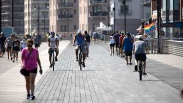 Bicyclists ride on the boardwalk in Long Beach
