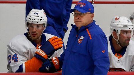 Islanders head coach Barry Trotz looks and Scott