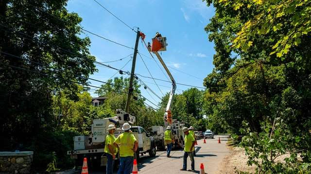 A utility crew restores power to angry residents